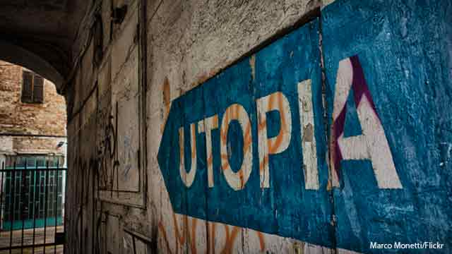 """Image shows word """"Utopia"""" in blue and white paint on a wall"""