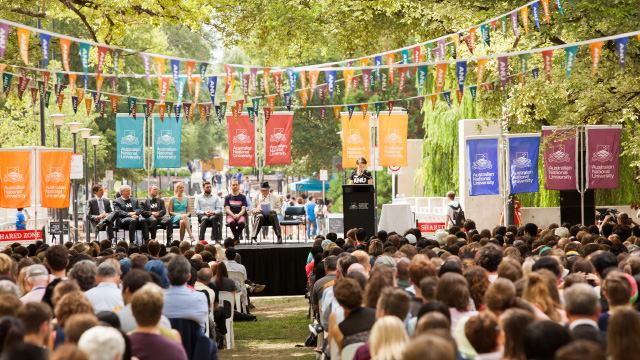 Image shows students sitting outside beneath colourful bunting and a stage on University Avenue