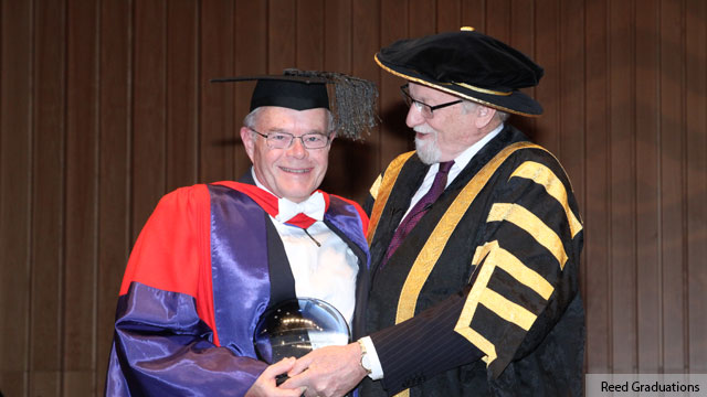 Professor Bob Goodin stands on left and receives glass award from Chancellor Gareth Evans. Both wear ceremonial academic robes