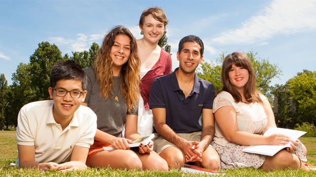 Image shows group of five smiling ANU students on lawns of campus
