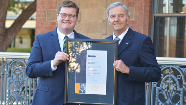 Image shows Daniel McKay and the Hon David Hawker. Both men are holding the framed scholarship