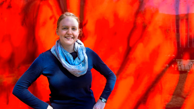 Image shows Dr Garnett wearing blue and standing in front of a red wall