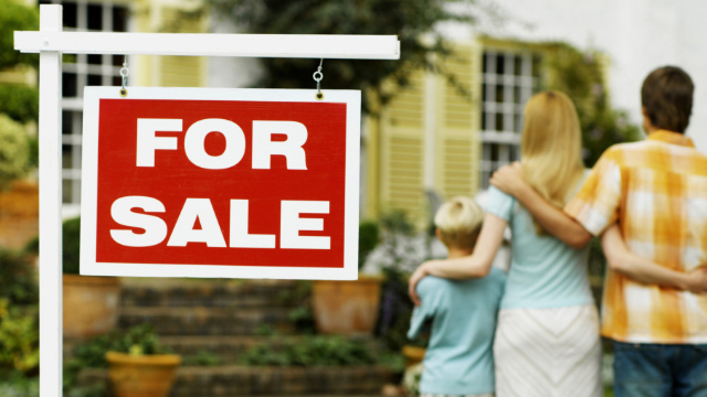 Red for sale sign and the backs of a boy, woman and man looking at a house