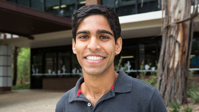 Image shows Matthew Jacob standing and smiling on campus