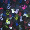 Painted handprints in white, green, blue, purples, red and pink on dark background