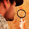 Archeologist inspecting wall inscription with magnifying glass