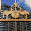 Australian Coat of Arms made from metal mounted on window; reflection of multi-story building in background